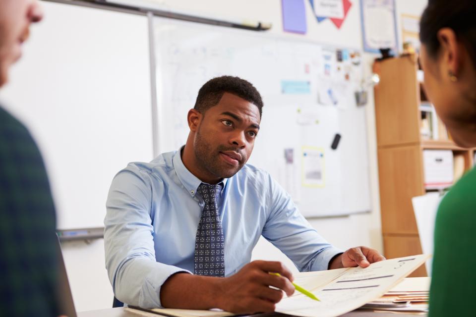 Teacher meeting with high school student
